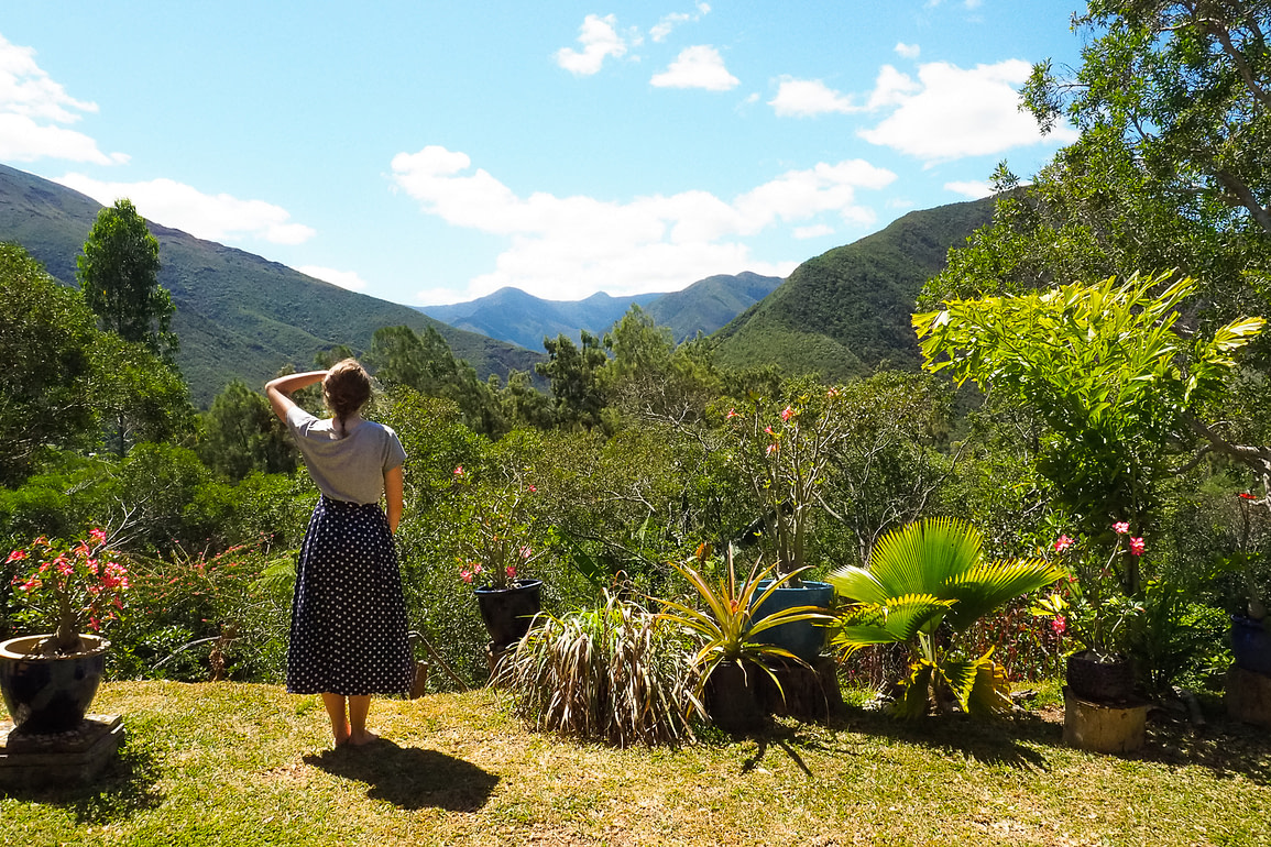 Me facing out into the distance with mountains and greenery surrounding.